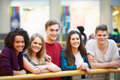 Group of friends hanging out in shopping mall smiling at camera Royalty Free Stock Images