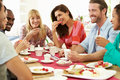 Group of friends having cheese and coffee at dinner party chatting to each other smiling Stock Photo