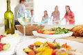 Group of friends having dinner party at home standing in background with close up food and drink Royalty Free Stock Photography