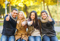 Group of friends having fun in autumn park summer holidays vacation happy people concept or couples and showing thumbs up Royalty Free Stock Photo