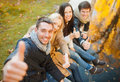 Group of friends having fun in autumn park summer holidays vacation happy people concept or couples and showing thumbs up Stock Photography