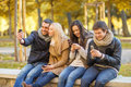 Group of friends having fun in autumn park summer holidays vacation happy people concept or couples with smartphone Stock Photo