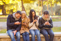 Group of friends having fun in autumn park summer holidays vacation happy people concept or couples with smartphones Royalty Free Stock Image
