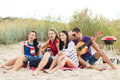 Group of friends having fun on the beach summer holidays vacation music happy people concept with guitar Stock Image