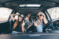 Group of friends having fun on the car. Singing and laughing in the car drive in city center Royalty Free Stock Photo