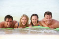 Group of friends having fun in sea on airbed Stock Photos