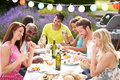 Group of friends having outdoor barbeque at home chatting to each other Royalty Free Stock Images