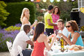 Group of friends having outdoor barbeque at home chatting to each other in garden Royalty Free Stock Photo