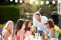 Group of friends having outdoor barbeque at home chatting to each other laughing Royalty Free Stock Image