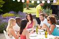 Group of friends having outdoor barbeque at home a conversation Royalty Free Stock Photo