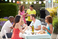 Group of friends having outdoor barbeque at home in the garden eating food Stock Photos