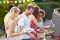 Group of friends having outdoor barbeque at home in garden serving food Royalty Free Stock Photo