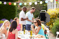 Group of friends having outdoor barbeque at home in garden sitting around table chatting Stock Images