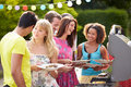 Group of friends having outdoor barbeque at home holding plates with food on smiling Royalty Free Stock Photos