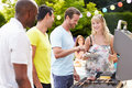 Group of friends having outdoor barbeque at home looking each other smiling Royalty Free Stock Photo
