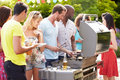 Group of friends having outdoor barbeque at home serving food in summertime Stock Photos