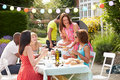 Group of friends having outdoor barbeque at home in summertime sitting around table Royalty Free Stock Image