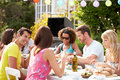 Group of friends having outdoor barbeque at home in summertime talking to each other Royalty Free Stock Images