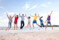 Group of friends jumping on the beach Royalty Free Stock Photo