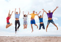 Group of friends jumping on the beach summer holidays vacation happy people concept Royalty Free Stock Photos
