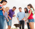 Group of friends making barbecue on the beach summer holidays vacation happy people concept having picnic and Royalty Free Stock Photography