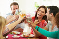 Group of friends making toast around table at dinner party holding glass wine smiling Stock Photo