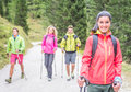 Group of friends making trekking excursion in the forest concept about seasonal leisure activity nature and people Royalty Free Stock Image