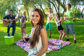 Group of friends partying in the park young college with a pretty young teenage girl foreground smiling at camera and Royalty Free Stock Photo