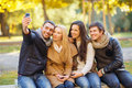 Group of friends with photo camera in autumn park summer holidays vacation travel and tourism concept or couples having fun Royalty Free Stock Photo