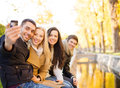 Group of friends with photo camera in autumn park summer holidays vacation travel and tourism concept or couples having fun Stock Images