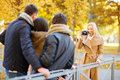 Group of friends with photo camera in autumn park summer holidays vacation travel tourism happy people concept or couples having Royalty Free Stock Image