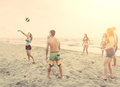 Group of friends playing with ball on the beach multiracial there are four girls and three boys a filipina girl and a spanish Stock Photos
