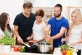 Group of friends preparing dinner diverse young together in the kitchen standing at the counter and hob cooking spaghetti and Royalty Free Stock Images