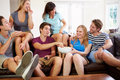 Group of friends relaxing on sofa at home together looking each other talking Stock Image