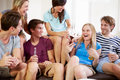 Group of friends relaxing on sofa at home together talking to each other Stock Images