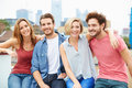 Group of friends relaxing together on rooftop terr terrace with arms around each other smiling Stock Photos