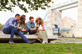 Group of friends relaxing by tower bridge in london Royalty Free Stock Photos