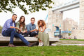 Group of friends relaxing by tower bridge in london Royalty Free Stock Photo