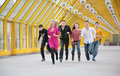 Group of friends runs on yellow footbridge Stock Images