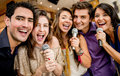 Group of friends singing karaoke at the bar Stock Images