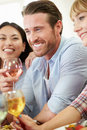 Group of friends sitting around table having dinner party close up smiling Royalty Free Stock Photo