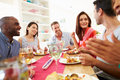 Group of friends sitting around table having dinner party at home whilst looking at each other chatting Royalty Free Stock Images