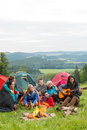 Group friends sitting tents campfire girl playing guitar Stock Image