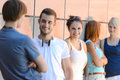 Group of friends students leaning against wall in row modern college Royalty Free Stock Images
