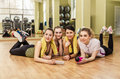 Group of girls in fitness class at the break happy laying floor one them is with smartphone hand Stock Photos