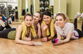 Group of girls in fitness class at the break happy laying floor one them is with smartphone hand Stock Image