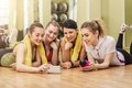 Group of girls in fitness class at the break happy looking smartphone Royalty Free Stock Photography