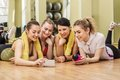Group of girls in fitness class at the break happy looking smartphone Stock Image