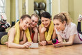 Group of girls in fitness class at the break happy looking smartphone Stock Images