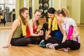 Group of girls in fitness class at the break looking smartphone Stock Photo